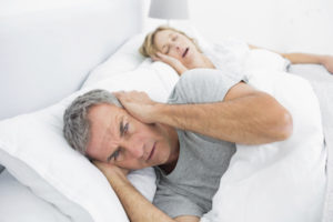 Annoyed man blocking his ears from noise of wife snoring because of sleep apnea symptoms